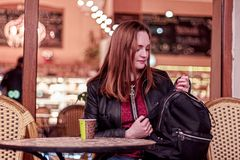 Młodej kobiety obsiadanie w wieczór w kawiarni i patrzeć czernić plecaka fotografia stock