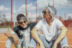 Młodej kobiety obsiadanie z jej synem przy boiskiem obrazy stock