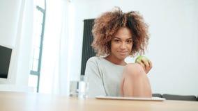 Młodej kobiety obsiadanie z zielonym jabłkiem w domu i ono uśmiecha się przy kamerą Fotografia Royalty Free