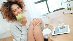 Młodej kobiety obsiadanie z zielonym jabłkiem w domu i ono uśmiecha się przy kamerą Obraz Stock