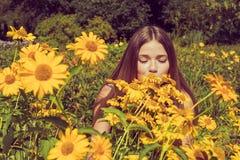 Młodej kobiety obwąchanie kwitnie Heliopsis w ogródzie Fotografia tonująca Obrazy Royalty Free