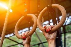 Młodej kobiety obwieszenie na gym pierścionkach obraz stock