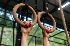 Młodej kobiety obwieszenie na gym pierścionkach zdjęcia royalty free