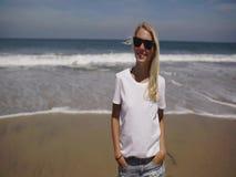 Młodej kobiety odprowadzenie na plażowej patrzeje kamerze i ono uśmiecha się zbiory