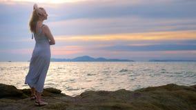 Młodej kobiety odprowadzenie na skalistym i cieszyć się widok zmierzch, bryzga machamy zbiory