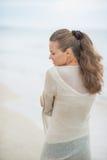 Młodej kobiety odprowadzenie na zimno plaży. tylni widok zdjęcia royalty free