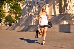 Młodej kobiety odprowadzenie z torba na zakupy w zmierzchu zdjęcia stock