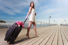 Młodej kobiety odprowadzenie z walizką na kołach zdjęcie royalty free