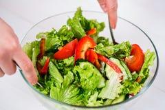 Młodej kobiety opatrunkowa jarzynowa sałatka z oliwa z oliwek na białym tle Obraz Stock