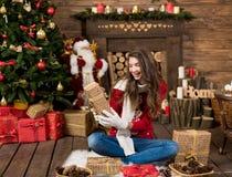 Młodej kobiety otwarcia teraźniejszości pudełko w wewnętrznym nowego roku studiu Fotografia Stock