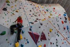 Młodej kobiety pięcie na postępowej pięcie ścianie indoors obraz royalty free