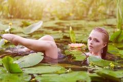 Młodej kobiety piękna portret w wodzie Dziewczyna z delikatnym makeup w jeziorze wśród lotuses i wodnych leluj plenerowy Obraz Stock