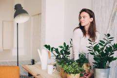 Młodej kobiety podlewania flowerpots w domu Przypadkowe styl życia serie w nowożytnym scandinavian wnętrzu Fotografia Stock
