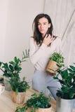 Młodej kobiety podlewania flowerpots w domu Przypadkowe styl życia serie w nowożytnym scandinavian wnętrzu Zdjęcia Royalty Free