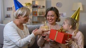 Młodej kobiety podmuchowa urodzinowa świeczka, otrzymywa teraźniejszość od kochającej rodziny zbiory