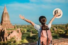 Młodej kobiety podróżny backpacker z kapeluszem, Azjatycka podróżnik pozycja na Pagodowych i patrzeją Pięknych antycznych świątyn fotografia stock