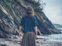 Młodej kobiety pozycja falezą na plaży Fotografia Stock