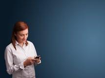 Młodej kobiety pozycja i pisać na maszynie na jej telefonie z kopii przestrzenią Zdjęcie Stock