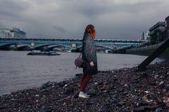 Młodej kobiety pozycja na brzeg rzeki w mieście Zdjęcia Royalty Free