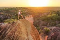 Młodej kobiety pozycja na górze wzgórza, wskazuje przy słońcem zdjęcia stock