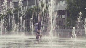 Młodej kobiety pozycja na jej głowie wśrodku fontanny zbiory