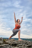 Młodej kobiety pozycja na kamieniu i ćwiczy joga blisko dużej rzeki Zdjęcie Stock
