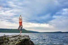 Młodej kobiety pozycja na kamieniu i robić joga ćwiczeniom zbliżamy rzekę Obrazy Royalty Free