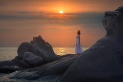 Młodej kobiety pozycja na skale i patrzeć słońce Zdjęcia Stock