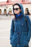 Młodej kobiety pozycja na ulicie zamazywał tło budynek spojrzenia i, ulica styl, fotografia royalty free