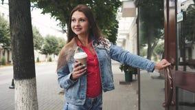 Młodej kobiety pozycja pić kawę, Przed sklep z kawą plenerowy zbiory