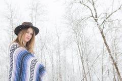 Młodej kobiety pozycja w śniegu z czecha stylu koc i kapeluszem Obrazy Stock