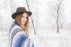 Młodej kobiety pozycja w śniegu z czecha stylu koc i kapeluszem Zdjęcie Royalty Free