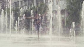 Młodej kobiety pozycja w drzewnej pozyci wśrodku fontanny zbiory wideo