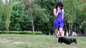 Młodej kobiety pozycja w parku z jej jamnika mały psim i opowiada na telefonie komórkowym zdjęcie wideo