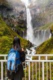 Młodej kobiety pozycji turystyczny spojrzenie przy i cieszyć się widok natura przy Kegon Spadamy w jesieni przy Nikko parkiem nar zdjęcia stock