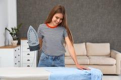 Młodej kobiety prasowanie odziewa na pokładzie zdjęcie stock