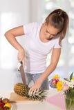 Młodej kobiety przecinania ananas zdjęcia royalty free
