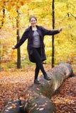 Młodej kobiety równoważenie na drzewnym bagażniku w lesie w spadku fotografia stock