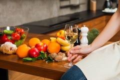 Młodej kobiety ręka trzyma szkło wino w kuchni Zdjęcia Stock