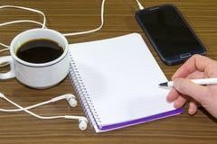 Młodej kobiety ręki mienia smartphone i pióra writing na notatniku tapetujemy przy sklep z kawą zdjęcia stock