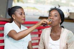 Młodej kobiety robić cieszy się napój jej przyjacielem obraz stock