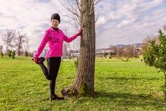 Młodej kobiety rozciąganie i nogi przed biegać na zimnej zimie, jesień spadku dzień w miastowym parku obrazy royalty free