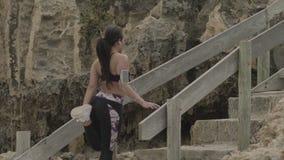 Młodej kobiety rozciąganie przed jogging w górę kroków na plaży przy chmurną pogodą przydatność swobodny ruch zdjęcie wideo