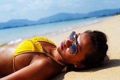 Młodej kobiety słońca kąpanie na piaskowatej plaży Tajlandia Fotografia Stock