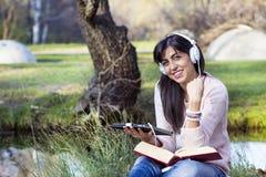 Młodej kobiety słuchająca muzyka z jej pastylką w jesień parku Zdjęcie Stock