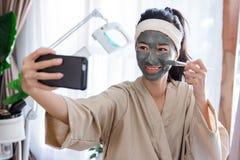Młodej kobiety selfie gdy używać twarzowego maskowego błoto zdjęcia royalty free