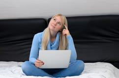 Młodej kobiety siedzący główkowanie na jej łóżku fotografia stock