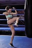 Młodej kobiety sprawności fizycznej kopanie przed uderzać pięścią torbę Obraz Stock