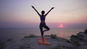 Młodej kobiety stojaki w joga pozie na górze blisko falezy z widokami świt, ocean lub zmierzch i Pok?j i zbiory