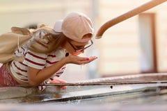 Młodej kobiety turystyczny odświeżenie jawną fontanną na gorącym letnim dniu obraz royalty free
